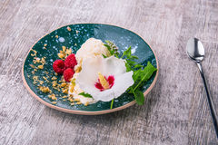 Cold vanilla ice cream with decorative flower and mint on a wooden background. A dessert with raspberries and nuts. Stock Photos