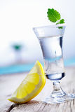 Cold vodka in frosted shot glass. Cold vodka in a frosted shot glass served with lemon chaser alongside a blue pool in summer Stock Photo