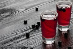 Cold vodka with red blackberry juice in two glasses royalty free stock image