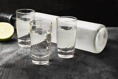 Cold vodka in shot glasses on a black background.  Stock Image