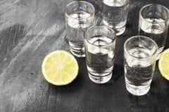 Cold vodka in shot glasses on a black background.  Stock Photo