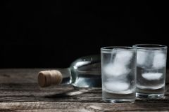 Cold vodka in shot glasses on a black background Stock Photos