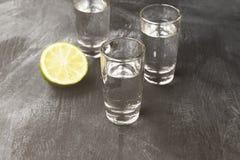 Cold vodka in shot glasses on a black background. Toned.  Stock Image