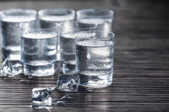 Cold vodka in shots. Small glass shots with vodka and ice cubes on wooden table Stock Photo