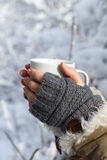 Cold and warm. Women's hands in gray fingerless knitted mittens and coat with white fur holding white cup of tea at the background of snowy forest. Close up Royalty Free Stock Photography
