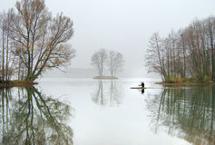 On cold water. The oarsman in a boat floats on lake in November Royalty Free Stock Photography