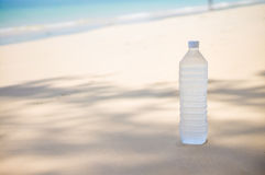 Cold water bottle with drops on it on tropical island beach Royalty Free Stock Photography