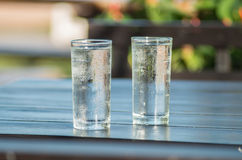 Cold water drink in the glass on wooden table Royalty Free Stock Image