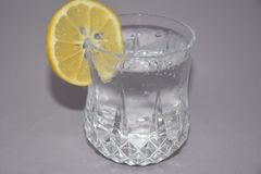 A cold water glass with lemon  on white. Glasses water drink lemon cold ice  liquid white transparent beverage clear alcohol clean blue food fresh cool healthy Stock Photography
