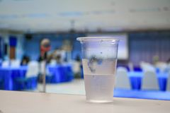 Cold water in glass-plastic in seminar conference room background. select focus with shallow depth of field royalty free stock image