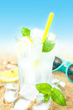 Cold water with lemon and ice on beach background Royalty Free Stock Photography