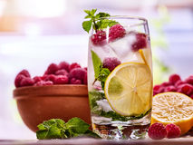 Cold water with lemon and mint leaf. Raspberries lemonade. Cold water with lemon and mint leaf. Fresh raspberries lemonade with lime slice and ice cubes Royalty Free Stock Photos