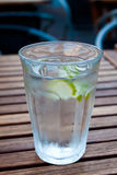 Cold water with lime. Glass of ice cold water standing on a hardwood table Stock Photo