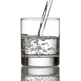 Cold water pour water to glass on white Royalty Free Stock Photos