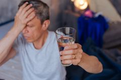 Unhappy mature man wanting water. Cold water. Selective focus of clean fresh water filled in glass which hold by painful man royalty free stock images