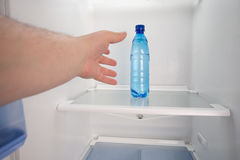 Cold water on a shelve in an empty fridge. Royalty Free Stock Photography