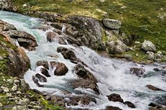 Cold water slashing through rocks. This ice cold short-drop water fall finds it's way across a typical Norwegian landscape full of rocks Stock Photo