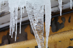 Cold weather concept with Icicles downspout on the roof. macro view. Soft focus Stock Photo