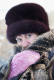 Cold weather. Woman muffles up in a fur collar Stock Photography