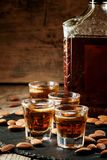 Cold whiskey with ice in a glass and a snack almonds, selective stock photography