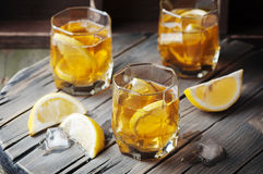 Cold whiskey with ice and lemon on the vintage table Stock Images