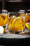 Cold whiskey with ice and lemon on the vintage table Royalty Free Stock Photography