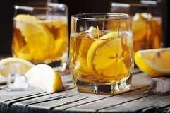 Cold whiskey with ice and lemon on the vintage table Royalty Free Stock Photos