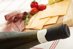Cold white wine with cheese and ham. Delicious prosciutto and ham plate with rosemary, grapes and a white wine bottle with waterdrops Stock Images