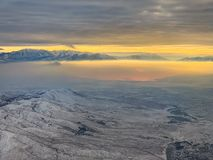 Snow covered mountains overlooking Salt Lake City in winter with glow of rising sun. Cold, white, winter landscape with mountains and Salt Lake City as the stock images