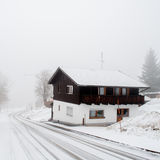 Cold winter. Wooden house in big snow royalty free stock image
