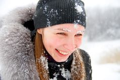 Cold winter, cold snow. Laughing girl with snow on her face staying in a winter woods Stock Image