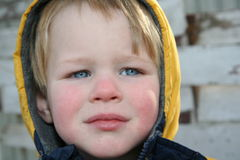 Cold Winter Day. Toddler Boy outside in winter looking sad, sparkling blue eyes stock images