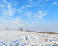 Cold Winter Day. A road leading to a farm on a cold winters day with blue sky and whispy clouds Stock Photography