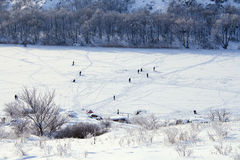 Cold winter. Frozen river. Peoples on ice. Cold winter. Frozen river. Lot of peoples on ice walking, fishing and even swiming in hole Royalty Free Stock Image