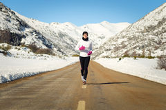 Cold winter running woman. Female athlete running in cold winter mountain road. Woman training for marathon outdoors wearing warm sportswear royalty free stock images