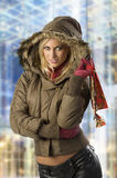 The cold winter shopping. Fashion shot of a young blond woman in winter jacket with hood and fur with shopping christmas bag Royalty Free Stock Photography