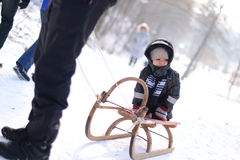 Cold winter sledge. Boy on sledge looking sadly or bored to side being pulled by adult Stock Image