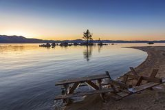 Cold Winter Sunset Lake Tahoe California Landscape Scenery. Sunset Landscape Scenic Winter View at Lake Tahoe Sandy Beach with ice on old frozen picnic bench royalty free stock photography