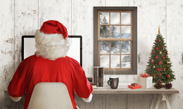 Cold winter time at Santa Claus home. Santa Claus work online on his computer Stock Photos