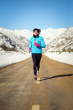 Cold winter woman running in road Royalty Free Stock Photos