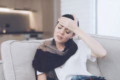 A cold woman sits on a light couch wrapped in a blue checkered whip. She holds her hand to her forehead. Closing his eyes royalty free stock images