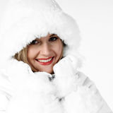 Cold Woman in Winter Coat. High Key shot of a woman wearing a fur lined coat & hood pulling up the collar Royalty Free Stock Photography