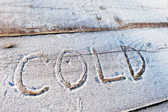 Cold written on a wooden background with frosts Royalty Free Stock Photos