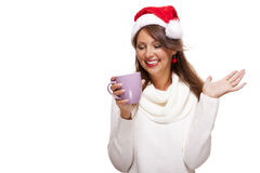 Cold young woman in a Santa hat sipping coffee tea Royalty Free Stock Image