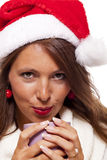 Cold young woman in a Santa hat sipping coffee tea Stock Photography
