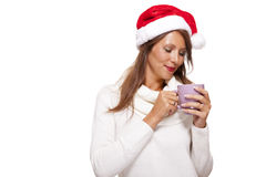 Cold young woman in a Santa hat sipping coffee tea Stock Photo