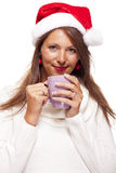 Cold young woman in a Santa hat sipping coffee tea Royalty Free Stock Images