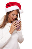 Cold young woman in a Santa hat sipping coffee tea Stock Image