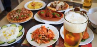 Colden öl på högväxt exponeringsglas med bubblor skummar och aptitretare Royaltyfri Bild