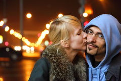 Coldly fall city. woman is kissing her man. Street of night coldly fall city. woman is kissing her man. focus on man's face Stock Photo